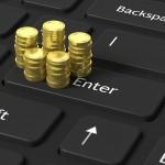 Stacks of golden coins on black laptop keyboard