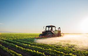 Tractor spraying soybean field